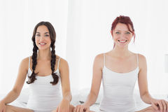 Two young women in white tank tops sitting on bed Stock Image
