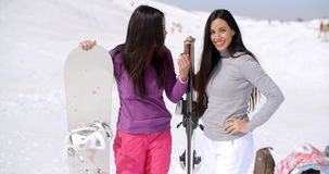 Two young women on a winter vacation. Standing laughing and talking in fresh snow at a ski resort holding their snowboards stock video