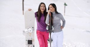 Two young women on a winter vacation. Standing laughing and talking in fresh snow at a ski resort holding their snowboards stock footage