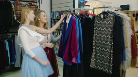 Two young women women customers choose clothes in shop. Two young women choosing clothes in a store. Communicate, looking at future purchases. HD video stock video footage
