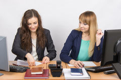 Two young women working in the office, one puts a piece of paper, the second in amazement staring at her. Two young pretty business women sitting at a office Royalty Free Stock Image