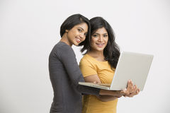 Two young women working posing with laptop Royalty Free Stock Image