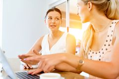Two young women working together at laptop Royalty Free Stock Images