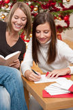 Two young women writing Christmas cards Royalty Free Stock Photography