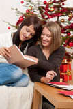 Two young women writing Christmas cards royalty free stock photo