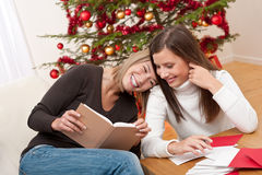 Two young women writing Christmas cards Stock Photos