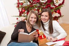 Two young women writing Christmas cards Royalty Free Stock Images