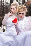 Two young womn in white dresses Stock Images
