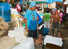 Two young workers moving huge ice blocks in the wet market royalty free stock photos
