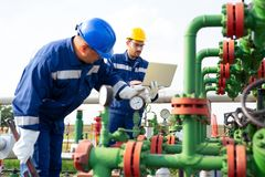 Two workers in the oilfield. Oil and gas concept. Two young workers in the oilfield. Oil and gas concept stock photos