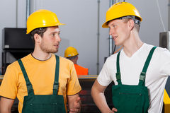 Two young workers in production area. Talking and looking at each other Royalty Free Stock Photo