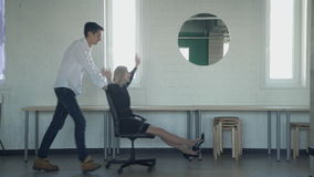 Two young workers rolling on office chair inside production floor. Man pushes woman on armchair with wheels in spacious room, playing race. Smiling people stock video footage