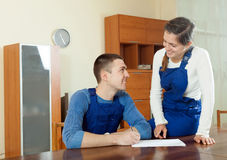Two  young  workers in uniform looking financial documents at ta Stock Photography