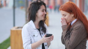 Two youthful attractive business womans, red-haired and brown-haired, talking and performing actions in smartphone. Urban landscape in background stock video footage