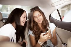 Two youthful friendly dark-haired girls,dressed in casual style, are sitting in the backseat of a fancy car and showing stock photography