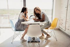 Two youthful pretty slim girls with dark hair,wearing casual outfit, sit at the table next to each other and chat in a stock photos