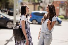 Two youthful pretty slim girls,wearing casual outfit,stand at the street and chat.  stock photo