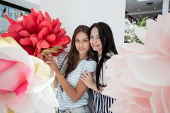 Two youthful smiling slim girls,dressed in casual outfit,stand next to each other in a lobby of a modern mall, royalty free stock images