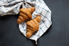Two yummy croissant lying on a black table. Also, there is twisted linen towel. Royalty Free Stock Photography