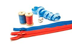Two zipper, meter, thimble and two spools of thread Royalty Free Stock Photography