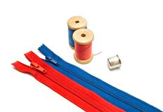 Two zipper, thimble and two spools of thread Royalty Free Stock Photo