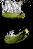 Two zucchinis splashing into water in front of black background Royalty Free Stock Photos