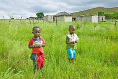 Two Zulu black boys in rural area of Zululand with village in background, South Africa Stock Photo