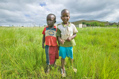 Two Zulu black boys in rural area of Zululand with village in background, South Africa Stock Images