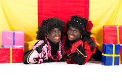 Two Zwarte Pieten lying. Zwarte Piet (Black Pete) is a character, part of a  Dutch tradition called Sinterklaas, which is celebrated at December the fifth Stock Image