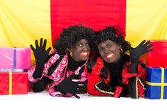 Two Zwarte Pieten lying. Zwarte Piet (Black Pete) is a character, part of a  Dutch tradition called Sinterklaas, which is celebrated at December the fifth Royalty Free Stock Image