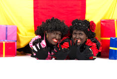 Two Zwarte Pieten lying. Zwarte Piet (Black Pete) is a character, part of a  Dutch tradition called Sinterklaas, which is celebrated at December the fifth Stock Photos