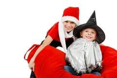 Twoboys con la bruja y el sombrero de Papá Noel Fotografía de archivo libre de regalías