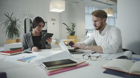 Twoemployees working in the office. Two employees working in the office. Sit  and  use digital tablet and phone stock footage