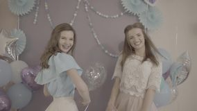 Two excited young attractive women in fancy pretty dresses with air balloons in hands turning around smiling in camera. Twoexcited young attractive women in stock video