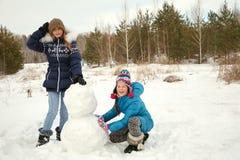 Twofunny flickor som bygger en snögubbe i vintern royaltyfri foto