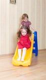 Twogirls ayant l'amusement placé sur la glissière de cour de jeu Images libres de droits