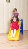 Twogirls having fun atop playground slide Royalty Free Stock Images