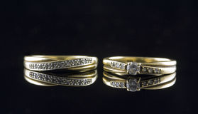 Twogold rings with gems. A shot of two gold rings with mirrored reflection Stock Photo