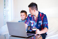 Twon brother buying online at home. Happy young family shopping on internet using laptop connection modern technology royalty free stock photo