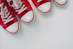 Twopair de la jeunesse rouge d'espadrilles sur une surface en bois blanche Photographie stock