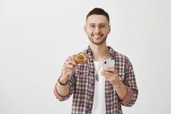 Ty musisz ono dostawać ten kartę Atrakcyjny młody coworker trzyma kredytową kartę i smartphone ono uśmiecha się szeroko przy, zdjęcie royalty free