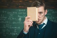 Ty musisz pamiętać Nauczyciel formalna odzież i szkieł spojrzenia mądrze, chalkboard tło Mężczyzna chwytów nieogolona książka wew zdjęcia royalty free