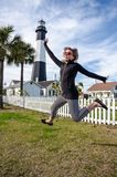 Tybee Island Light House in coastal Georgia. Adult woman jumps in front of the lighthouse, concept for excitement, joy and fun. Tybee Island Light House in stock photo