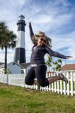 Tybee Island Light House in coastal Georgia. Blonde woman jumps in front of the lighthouse. Concept for excitement, joy and fun stock photography
