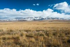 Tybetańscy średniogórza i odległe śnieżne góry blisko Daotanghe cit Zdjęcia Stock