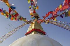 Tybetański buddysta barwiąca modlitwa zaznacza na Bodnath Świątynnej stupie na tle czysty niebieskie niebo zdjęcie royalty free