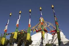 Tybetański buddysta barwiąca modlitwa zaznacza na tle świątynia Bodnath stupa jasny niebieskie niebo i obraz stock