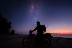 Tyck om att rida cykeln under det milkyway under skymning Fotografering för Bildbyråer
