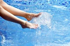 Tyck om den härliga flickan som kopplar av i simbassängen, ben av kvinnan i vatten royaltyfri foto