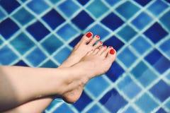 Tyck om den härliga flickan som kopplar av i simbassängen, ben av kvinnan i vatten royaltyfria foton